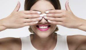 beauty woman smiling hiding her eyes with gel nails on white