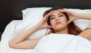 sick woman on bed massaging her head to relieve pain or stress