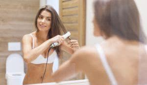 Smiling woman straightening hair in front of mirror