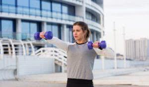 Sportive young woman working out outside in a big city