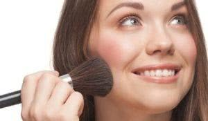 Close-up portrait of young beautiful woman with brush for blush or for powder. Pretty woman applying makeup