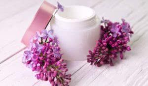 Pot of moisturizing cream with lilac flowers on wooden background