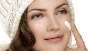 beautiful model applying a creme on face protection from winter cold on white